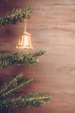 La caduta della campana degli ornamenti di Natale sull'albero di Natale ha fondo di legno dello spazio Immagini Stock Libere da Diritti