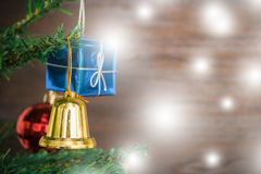 La caduta della campana degli ornamenti di Natale sull'albero di Natale ha fondo di legno dello spazio Immagine Stock