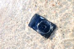 La caduta della macchina fotografica all'acqua di mare Immagine Stock