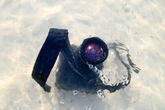 La caduta della macchina fotografica di DSLR all'acqua di mare Fotografia Stock