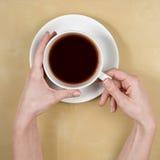 la Caffè-femmina passa la tenuta della tazza di caffè Fotografie Stock