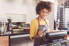 La caissière gaie de jeune femme travaille en café Image stock