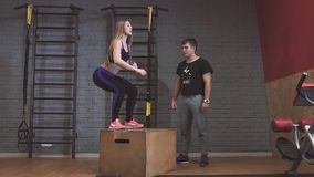 La caja atractiva de la gente de los deportes salta mientras que se resuelve en gimnasio almacen de video