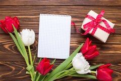 La caja con el presente, el Empty tag y los tulipanes rojos y blancos brillantes fluyen Foto de archivo