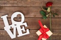 La caja con la cinta roja y subió en un fondo de madera, concepto del día de tarjeta del día de San Valentín Imágenes de archivo libres de regalías