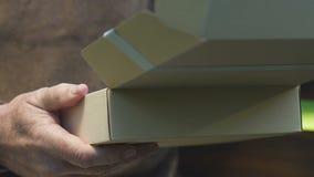 La caja de cartón de apertura del viejo hombre con la letra, recibió el paquete de niños almacen de metraje de vídeo