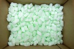 La caja de empaquetado grande llenó de muchas pelotillas blancas de la espuma de poliestireno foto de archivo