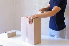 La caja de la cinta del pegamento del hombre joven y toma el paquete en las manos, colocándose en P Imagenes de archivo