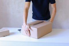 La caja de la cinta del pegamento del hombre joven y toma el paquete en las manos, colocándose en P Fotos de archivo