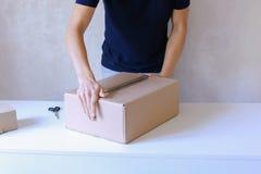 La caja de la cinta del pegamento del hombre joven y toma el paquete en las manos, colocándose en P Imagen de archivo