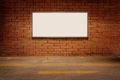 La caja de luz o el tablero blanco en la pared y la calle del grunge del ladrillo suela el fondo Imagen de archivo