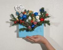 La caja de madera azul llenada de las decoraciones del árbol de navidad, y ramas del abeto en una mano femenina Foto horizontal b imagenes de archivo