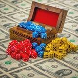 La caja de madera vieja llenó de los dados del juego en una hoja del dinero Imágenes de archivo libres de regalías