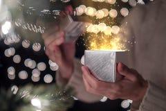 La caja de regalo abierta de la Navidad de la hembra con la luz mágica del oro en bokeh enciende el fondo Imagen de archivo libre de regalías