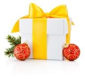 La caja de regalo blanca ató la cinta amarilla y la chuchería de la Navidad aisladas Foto de archivo
