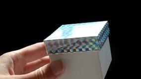 La caja de regalo blanca con la cubierta escocesa del arco iris, idea de DIY, la caja se abre a mano almacen de video