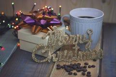 La caja de regalo blanca, taza azul, la inscripción casa la Navidad Foto de archivo