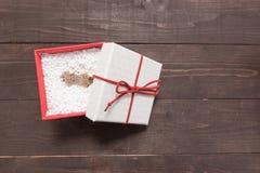 La caja de regalo blanca y roja está en el fondo de madera con el SP vacío Fotos de archivo libres de regalías