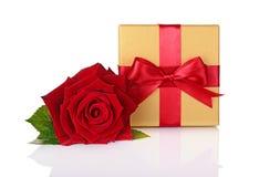 La caja de regalo clásica con el lazo de satén rojo y hermoso de oro subieron Imágenes de archivo libres de regalías