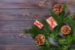 La caja de regalo con el abeto ramifica en fondo de madera Fotos de archivo libres de regalías