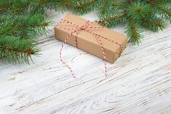 La caja de regalo con el abeto ramifica en la opinión superior del fondo de madera Imagen de archivo libre de regalías