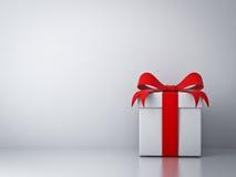 La caja de regalo con el arco rojo de la cinta y vacia el fondo blanco de la pared Imagen de archivo libre de regalías
