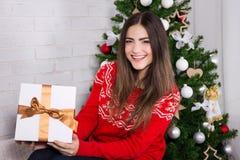 La caja de regalo de la abertura de la mujer joven cerca adornó el árbol de navidad Foto de archivo