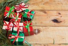 La caja de regalo de la Navidad con verde se va en el fondo de madera Imagen de archivo libre de regalías