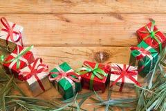 La caja de regalo de la Navidad con verde se va en el fondo de madera Fotografía de archivo
