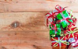 La caja de regalo de la Navidad con verde se va en el fondo de madera Fotos de archivo