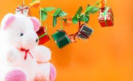 La caja de regalo de la Navidad, peluche refiere el fondo anaranjado Fotografía de archivo libre de regalías