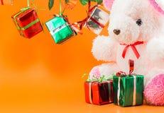 La caja de regalo de la Navidad, peluche refiere el fondo anaranjado Fotos de archivo