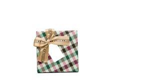 La caja de regalo del modelo de la tela escocesa con el arco beige de la cinta y la tarjeta de felicitación en blanco aislados en Imagenes de archivo
