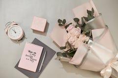 La caja de regalo, el despertador y el rosa subieron las flores en la opini?n de sobremesa blanca en estilo puesto plano Tarjeta  fotos de archivo libres de regalías