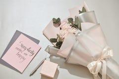 La caja de regalo, el despertador y el rosa subieron las flores en la tabla blanca fotos de archivo libres de regalías