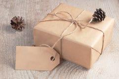 La caja de regalo embaló el papel marrón y la guita con la etiqueta en blanco adornó conos de abeto en la tabla de madera blanca Fotos de archivo libres de regalías