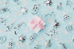 La caja de regalo en fondo azul de la Navidad adornó la opinión superior de las estrellas del confeti y de la plata Endecha plana Fotografía de archivo libre de regalías