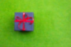 La caja de regalo en fondo verde blured para el fondo Imagen de archivo
