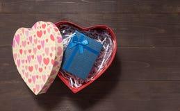 La caja de regalo está en caja del corazón, en el fondo de madera con el SP vacío Imagen de archivo libre de regalías