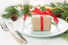 La caja de regalo de la Navidad en la placa con los cubiertos y el abeto ramifica en la tabla de madera blanca Imagenes de archivo