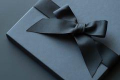 La caja de regalo negra en una oscuridad puso en contraste el fondo, adornado con a Imagenes de archivo