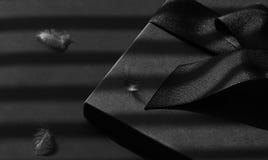 La caja de regalo negra en una oscuridad puso en contraste el fondo Fotografía de archivo libre de regalías
