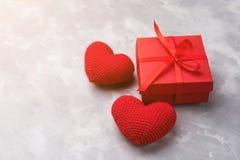 La caja de regalo roja con dos hizo punto corazones cerca mintió en fondo texturizado gris imagen de archivo libre de regalías
