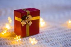 La caja de regalo roja con la guirnalda caliente se enciende en backgroun hecho punto blanco Imagen de archivo