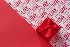 La caja de regalo roja del backround del día de tarjetas del día de San Valentín con el fondo rojo de la cinta y las letras aman Imagenes de archivo