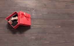 La caja de regalo roja está en el fondo de madera con el espacio vacío Foto de archivo libre de regalías