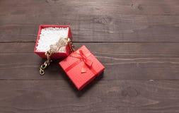 La caja de regalo roja está en el fondo de madera con el espacio vacío Imagen de archivo