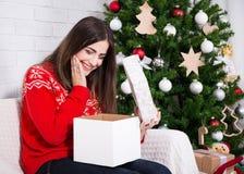 La caja de regalo sorprendida feliz de la abertura de la mujer cerca adornó la Navidad Imágenes de archivo libres de regalías