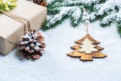 La caja de regalos con clase de la Navidad presenta en papel marrón con los juguetes y la decoración del Año Nuevo en la arpiller Foto de archivo