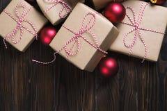 La caja de regalos de la Navidad presenta con las bolas rojas en fondo de madera fotos de archivo libres de regalías